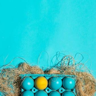 青いテーブルの上の干し草のラックにカラフルなイースターエッグ