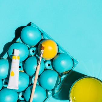 Пасхальные яйца в стойке с кистью и стаканом воды на столе