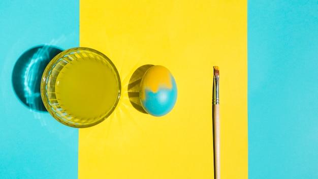 Красочное пасхальное яйцо с кистью и стаканом воды на ярком столе
