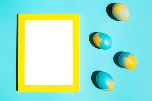 青いテーブルの上の空白の枠とカラフルなイースターエッグ