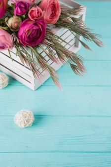 Розовые цветы с ветвями растений в коробке на столе