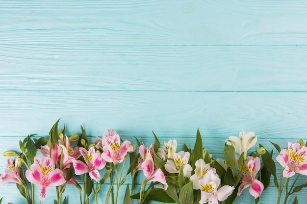 青い木製のテーブルの上に散らばってピンクの花