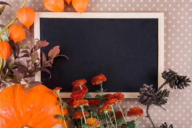 テーブルの上の空白の黒板とさまざまな植物