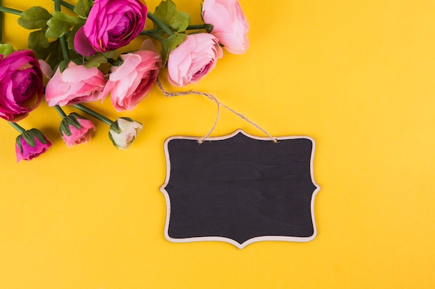 黄色のテーブルの上の小さな黒板とピンクのバラの花