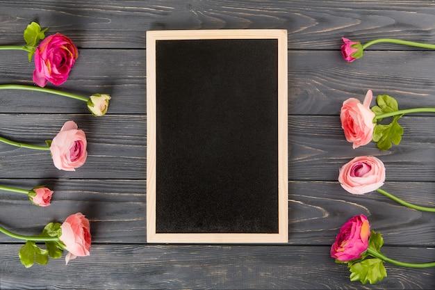 木製のテーブルの上の大きな黒板とピンクのバラの花