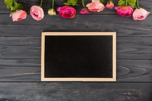 木製のテーブルに大きな黒板とバラの花