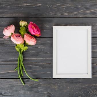 木製のテーブルの上の空白のフレームとピンクのバラの花