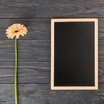 テーブルの上の空白の黒板とオレンジのガーベラの花