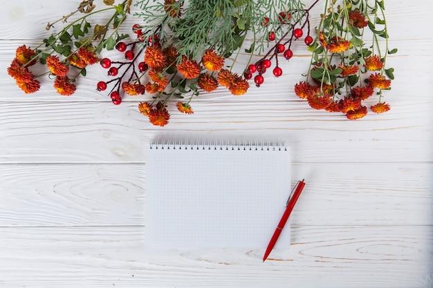 Красные цветы с пустой блокнот и ручка на столе
