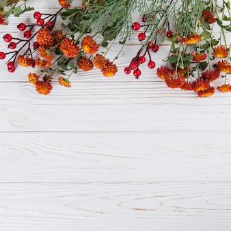 Красные цветы с ягодами разбросаны по деревянному столу
