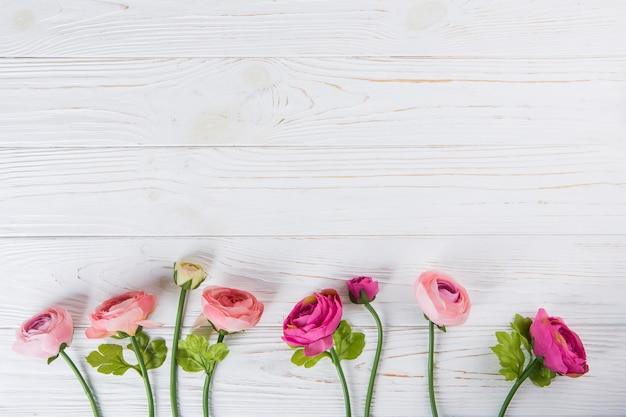 ピンクのバラの花が木製のテーブルの上に散らばって