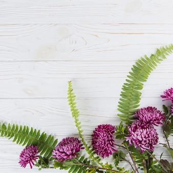 テーブルの上の紫色の花と緑のシダの葉