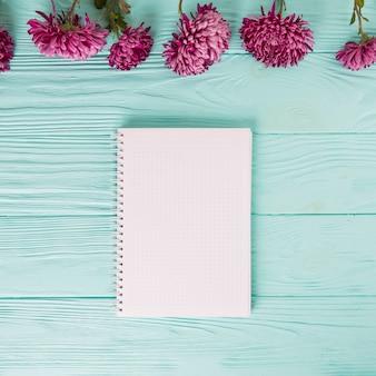 青いテーブルの上の空白のノートブックと紫の花