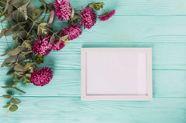 青い木製のテーブルの上の空白のフレームと紫の花