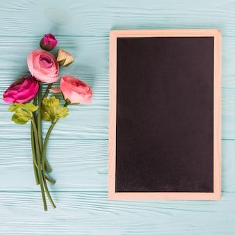 青い木製のテーブルに黒板とピンクのバラの花