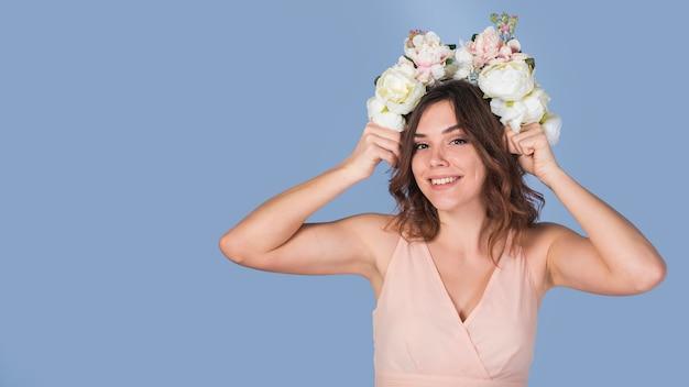 頭の上の新鮮な花のドレスで陽気な若い女性