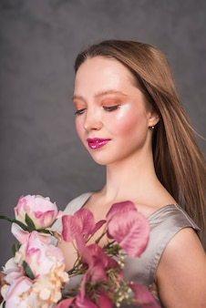 Молодая чувственная женщина с красивым цветочным букетом
