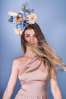 美しい花の花輪を持つイブニングドレスの若い女性