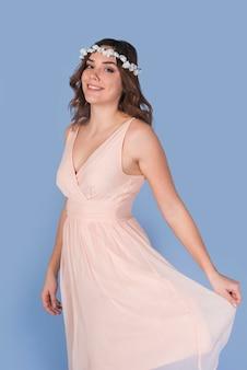 美しい花の花輪を持つピンクのドレスの若い幸せなブルネットの女性