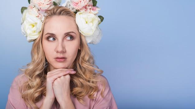 美しい花の花輪を持つ若い恐ろしいブロンドの女性