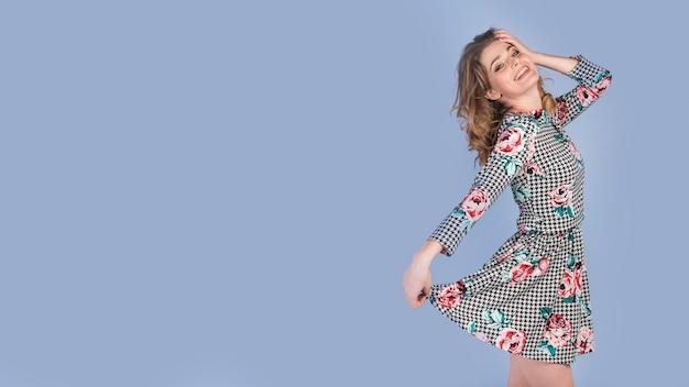 Счастливая молодая леди держит юбку элегантного платья