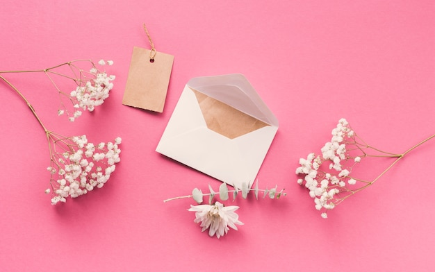 ピンクのテーブルの上の封筒と花の枝