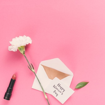 Счастливый женский день надпись с конвертом и цветок на розовом столе