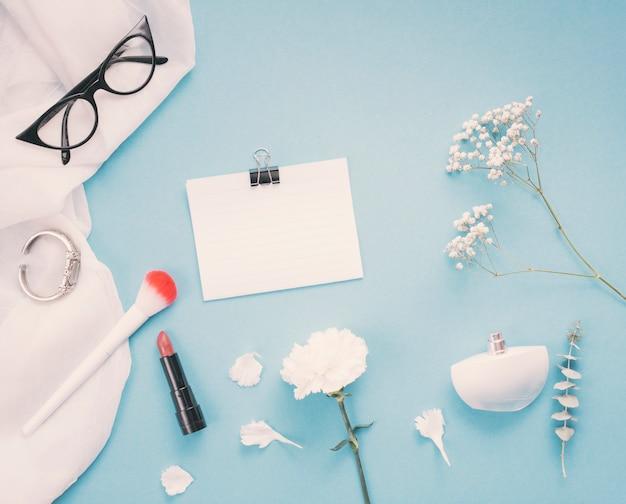 花とテーブルの上の化粧品の紙