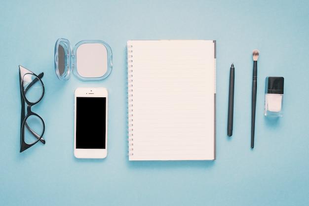 ノートブックとテーブルの上の化粧品を持つスマートフォン