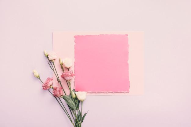 テーブルの上のバラの花と小さな紙