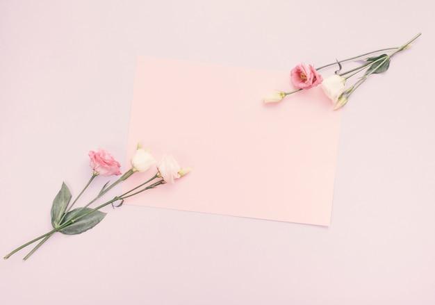 テーブルの上の明るい花と空白の紙シート