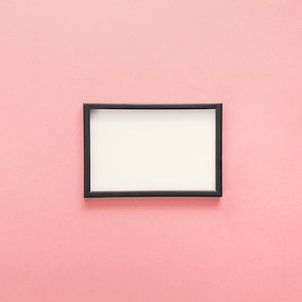 Маленькая пустая рамка на розовом столе