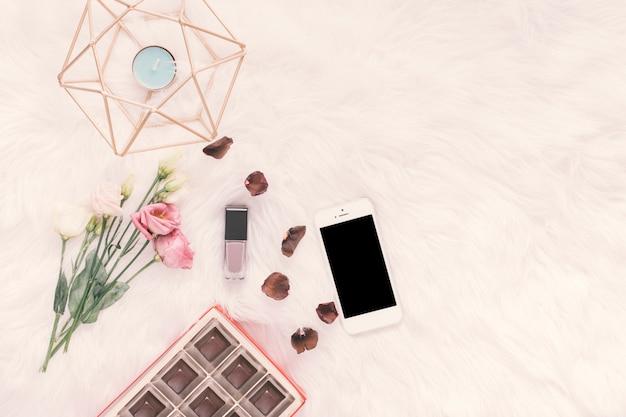 Смартфон с розами и шоколадными конфетами на одеяле