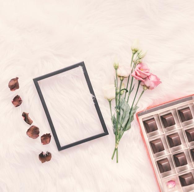 Пустая рамка с розами и шоколадными конфетами на одеяле