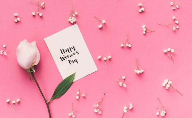 バラの花と紙の上の幸せな女性の日碑文