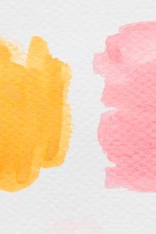 Желтые и красные акварельные пятна на белой бумаге