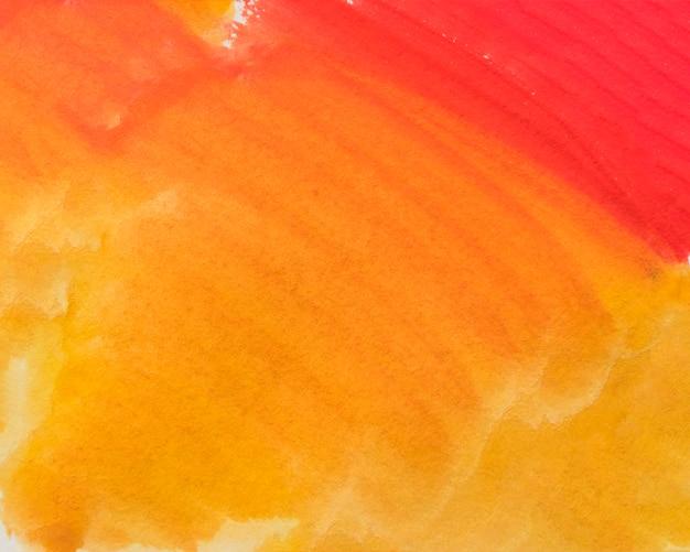 抽象的な塗られた黄色とオレンジ色の水彩画の濡れた背景