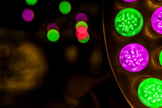 輝く緑とピンクの背景に電球