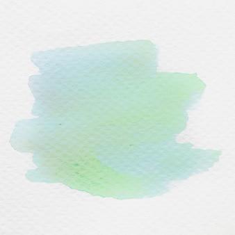 白いキャンバス紙の上の緑の水彩画のクローズアップ