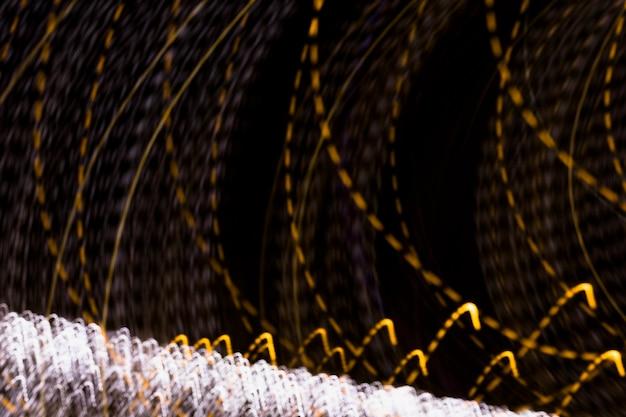 背景のフレーム全体を覆うライトのカーブシェイプゴールデントレイル