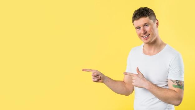 黄色の背景に対して彼の指を指している若い男の笑みを浮かべてください。