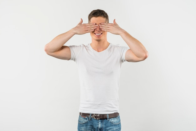 白い背景で隔離された彼の目を覆っている笑顔の若い男