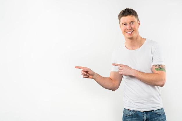 白い背景で隔離されたカメラを探している指を指している若い男の肖像