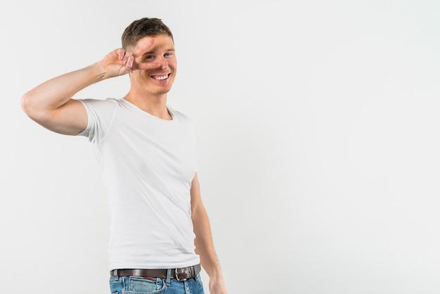 白い背景の上の彼の片目の前で平和のジェスチャーを作る若い男