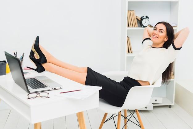 リラックスした女性のオフィスのテーブルに足を入れて