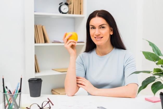 オフィスでアップルと座っている若い女性