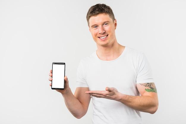 白い表示画面を持つこの新しいスマートフォンを提示する若い男の笑みを浮かべてください。