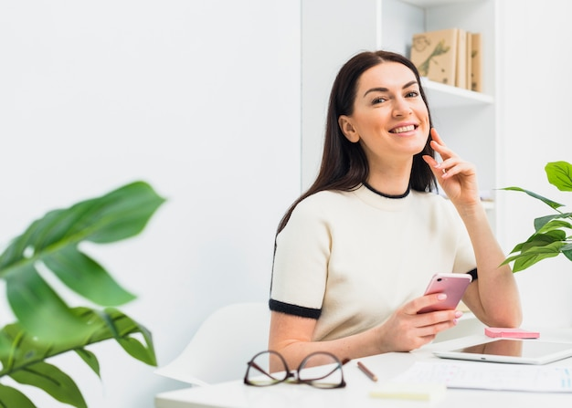 Женщина сидит с смартфон за столом в офисе