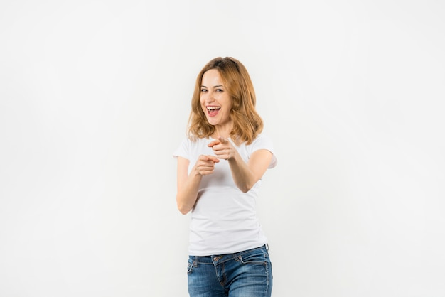 白い背景で隔離のカメラに向かって彼女の指を指している若い女性の笑みを浮かべてください。