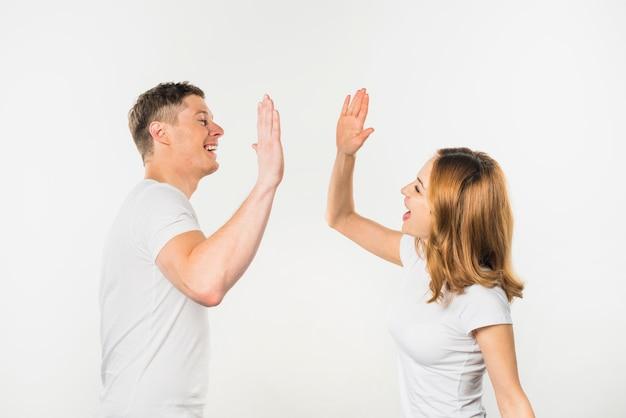 白い背景で隔離のお互いにハイタッチを与える若いカップルの笑顔